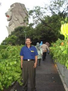 Penulis berfose di sisi patung Merlion, Singapura (Foto: Ist)